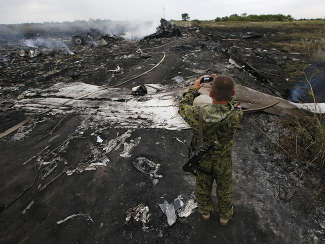 The aftermath ... an armed pro-Russian separatist takes pictures at the site of a Malaysia Airlines Boeing 777 plane crash, MH17, near the settlement of Grabovo in the Donetsk region. Picture: Picture Media