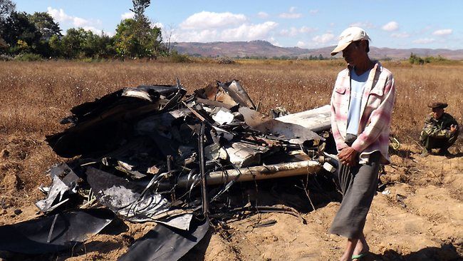A local residence looks at wrecked parts of Air Bagan passenger plane in Heho, Shan State, Myanmar, Tuesday, Dec. 25, 2012. The Air Bagan flight packed with Christmas tourists crash-landed on a road in central Myanmar on Tuesday, killing two people and injuring 11, officials said. Four foreigners were among the injured, state television reported. It said the fatalities included an 11-year-old passenger believed to be a Myanmar citizen and a man riding a motorcycle on the road where the plane came down. (AP Photo)
