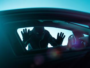 Car Robber Concept Photo. Robber Looking Thru Car Window. Carjacking Theme.