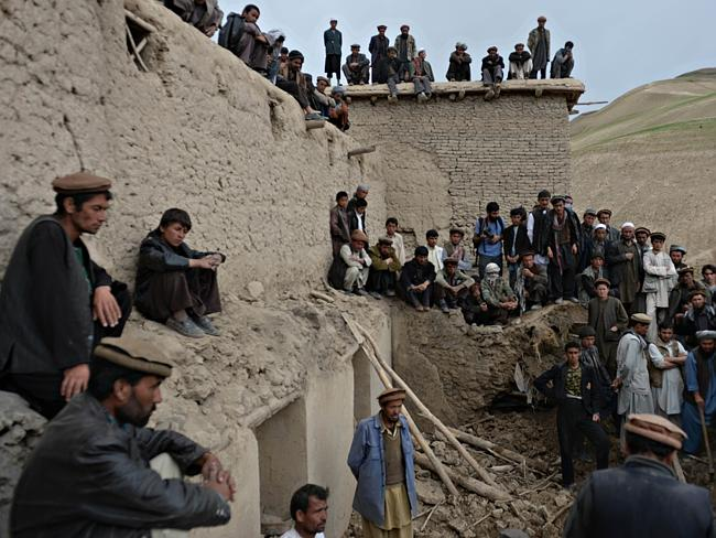 Shocked...Afghan villagers look on as rescuers search desperately for survivors trapped under the mud in Argo district of Badakhshan province. Picture: AFP