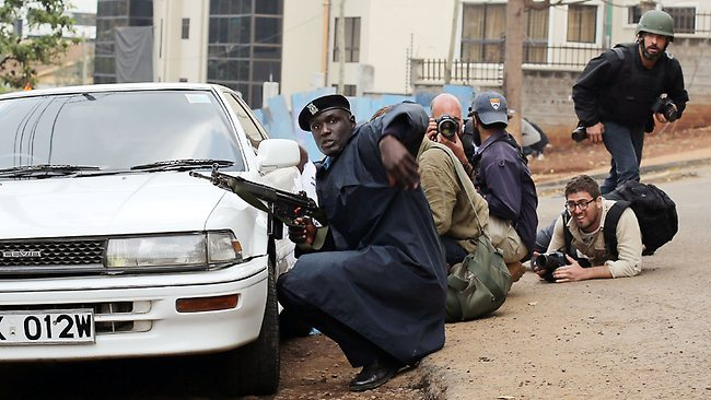 Kenyan security personnel and journalists duck behind a vehicle as heavy gunfire erupts from the Westgate Mall in Nairobi.