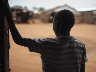 """In this photo taken Saturday, May 13, 2017, thirteen-year-old boy Batista, who five months ago was drugged and raped in the middle of the night, stands in the doorway of a psychosocial support clinic in a camp for the internally-displaced in Wau, South Sudan. Four years into South Sudan's devastating civil war, the world's youngest nation is reeling from sexual violence on a """"massive scale,"""" a new Amnesty International report says Monday, July 24, 2017. (AP Photo/Bruno Bierrenbach Feder)"""