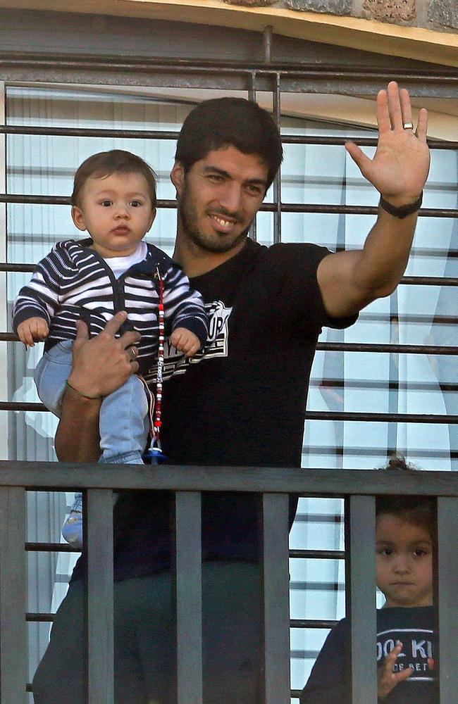 Uruguay's striker Luis Suarez greets fans from his mother's home in Lagomar.