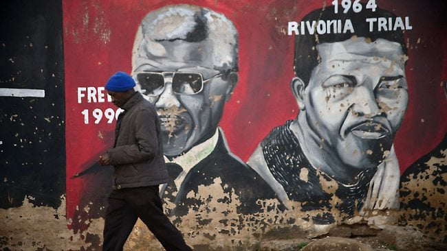 """A man walks past a mural of former President Nelson Mandela in Soweto . It is Mandela's fourth hospital stay since December and the use of the word """"serious"""" to describe his condition has intensified concerns about the health of a man revered around the world as a symbol of perseverance and reconciliation. AFP PHOTO / MUJAHID SAFODIEN"""