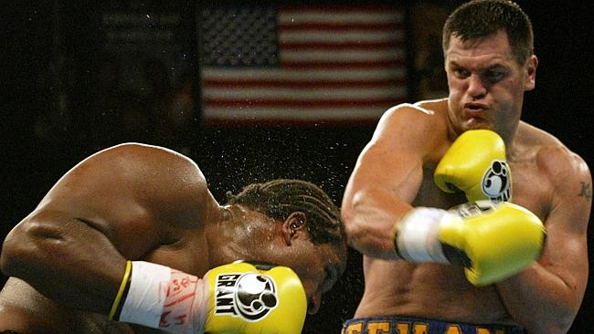 Lamon Brewster (L) takes a right to the head from Kali Meehan in 2004.