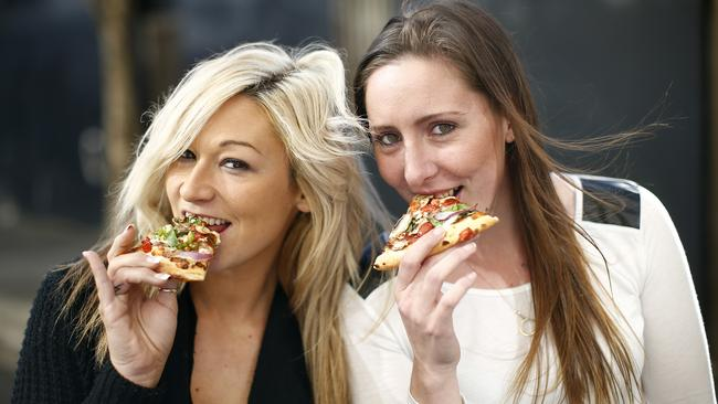 Brooke Cohen and Samantha Micallef tuck into slices of pizza. Picture: Bradley Hunter
