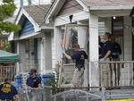 Cleveland's House of Horrors: Members of the FBI evidence response team carry out the front screen door from the house where three women who vanished a decade ago were found safe as police arrested three brothers accused of holding the victims against their will. Photo: AP/Tony Dejak