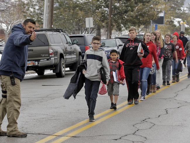 A police officer directs students down the street following the school lockdown at Mueller Park Junior High, Utah. Picture: AP