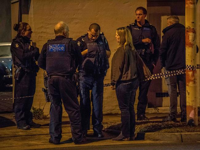 A woman, believed to be a relative of the deceased, speaks to police. Picture: Jake Nowakowski