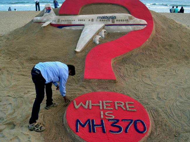 Aviation mystery ... Indian sand artist Sudarsan Pattnaik creates a sand sculpture of the missing Malaysian airliner MH370 on Puri beach in eastern Odisha state. Picture: AFP/JK Jagdev