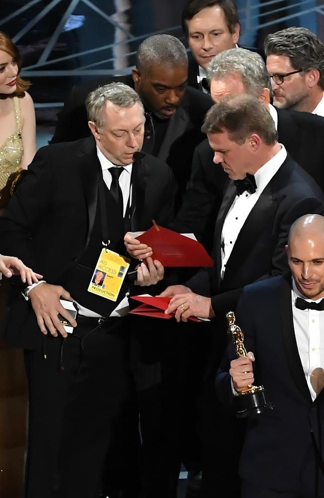 La La Land producer Fred Berger speaks at the microphone as production staff and representatives from PricewaterhouseCoopers scrambled on stage to work out what happened. Picture: Getty Images