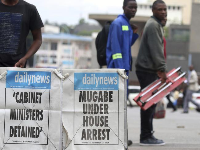 People pass a newspaper headline in Harare, Zimbabwe. Picture: AP