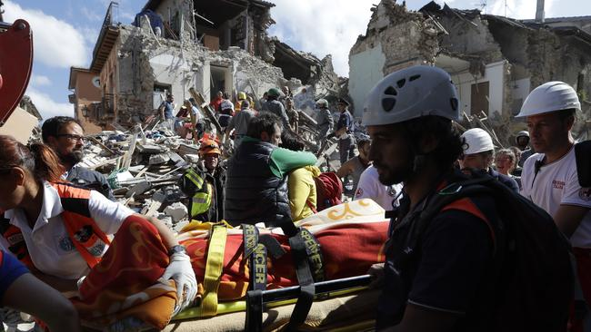 Rescuers recover a victim from a crumbled building in Amatrice, central Italy. Picture: AP/Alessandra Tarantino.