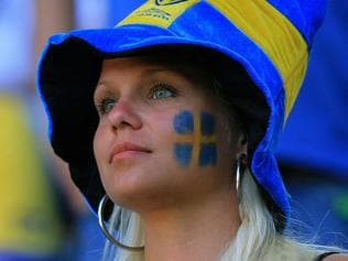 A Swedish football supporter wears colours of her team in Dortmund Stadium, 10/06/2006, prior to the 2006 World Cup group B match between Trinidad and Tobago and Sweden. AFP PHOTO / ODD ANDERSEN