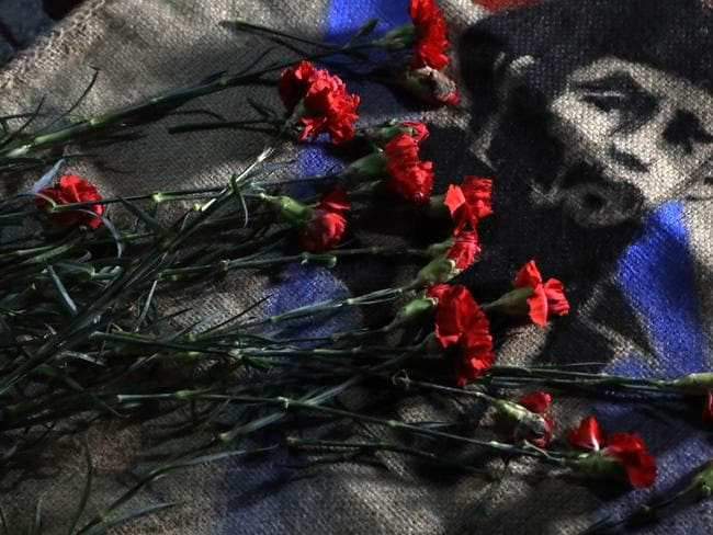 Roses are placed by members of Mexico's communist party atop an image of late Cuban President Fidel Castro, outside the Cuban Embassy in Mexico City. Picture: Rebecca Blackwell/AP