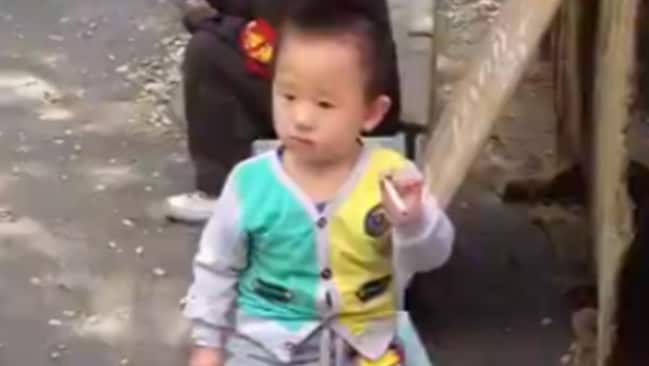 Heartbreaking ... the toddler puffs on a cigarette as he sits at his family's market stall.