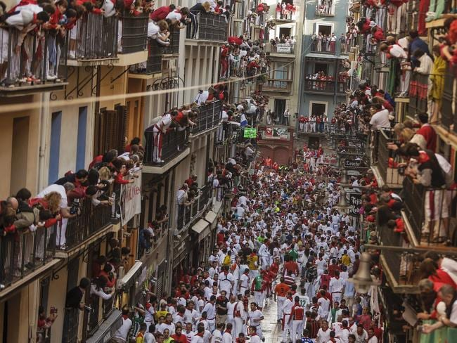 Revelers on Estafeta Street wait for the bulls, in Pamplona, Spain.