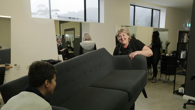 Noah Kemp, 13, helping Debby Armstrong of NVS Hairdressers in Huonville to move the furniture to higher ground while waiting for his haircut. Debbie's salon was hit hard by the 2016 flood, so she's not taking chances in this heavy rain. Picture: MATHEW FARRELL