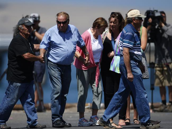 SHOCK: Damien Little's devastated parents Ken (in blue shirt, left) and Sue Little hold hands after their heartbreaking visit with friends to the memorial at the wharf. Picture: DEAN MARTIN