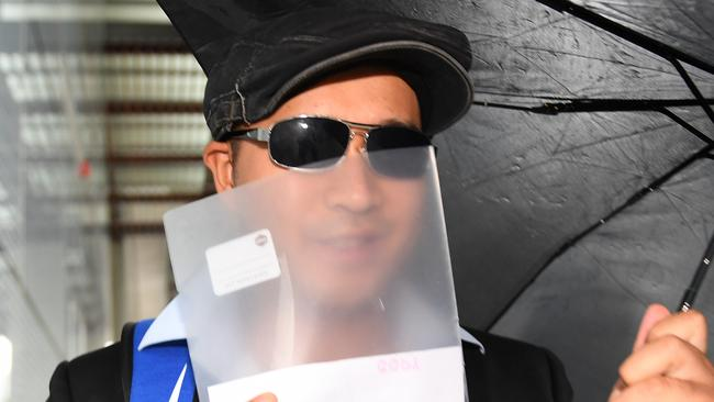 Dae Ik Kim tries to conceal his face as he leaves District Court in Brisbane today. Picture: Dan Peled/AAP