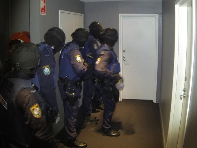 Armed police prepare to make their raid.