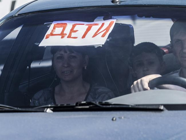 "Danger zone ... ar displays a sign reading ""deti"" (""children"") as people leave their home after shelling between pro-Russian militants and Ukrainian forces near the crash site of MH17, on July 28. Picture: Bulent Kilic"