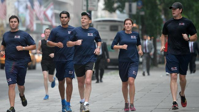 Running his own show ... Prime Minister Tony Abbott takes an early morning jog through Central Park with members of the New York fire department. Picture: Jake Nowakowski