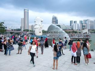 Singapore, Singapore - April 10, 2016: Afternoon view of people watching the Singapore Merlion statue at Marina Bay against Singapore skyline. The Merlion is a well known marketing icon of Singapore depicted as mythical creature with a lion's head and a body of a fish.
