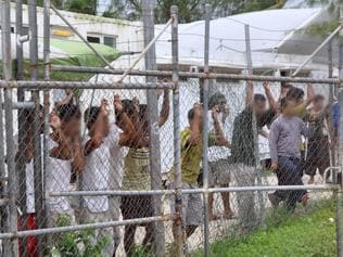 **FILE** A March 21, 2014 file image of Asylum seekers staring at media from behind a fence at the Oscar compound in the Manus Island detention centre, Papua New Guinea. Manus Island detainees will receive $70 million in the settlement of a class action against the Australian government, Wednesday, June 14, 2017. (AAP Image/Eoin Blackwell) NO ARCHIVING