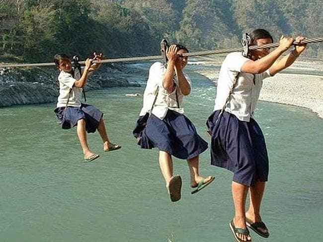 Nepalese girls float high above rivers on their way to school. These bridges are built at a fraction of the cost of suspended bridges and enable hill tribe children to cover the distances to school each day. Picture: justgiving.com