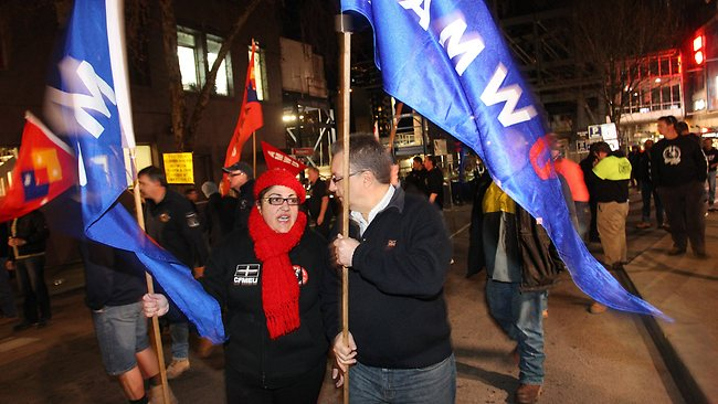 Other unionists carry flags in support of the CFMEU workers. Picture: Jake Nowakowski