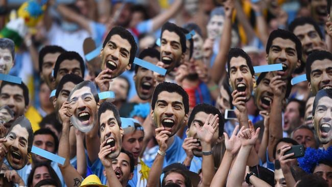 Uruguay fans hold up and wear Luis Suarez masks ahead of the match against Colombia.