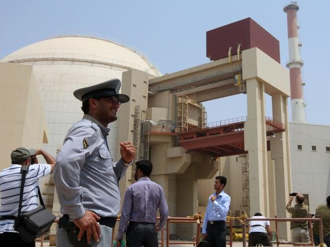 An Iranian security man stands next to journalists outside the reactor building at the Russian-built Bushehr nuclear power plant in southern Iran. Picture: Atta Kenare