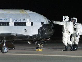 This picture provided by the US Air Force shows personnel inspecting the X-37B, the Air Force's first unmanned re-entry spacecraft, after landing on December 3, 2010 at Vandenberg Air Force Base in California. The X-37B, named Orbital Test Vehicle 1 (OTV-1), conducted on-orbit experiments for more than 220 days during its maiden voyage, and fired its orbital maneuver engine in low-earth orbit to perform an autonomous reentry before landing, according to the Air Force. AFP PHOTO/US AIR FORCE/HO ++RESTRICTED TO EDITORIAL USE � NOT FOR SALE FOR MARKETING OR ADVERTISING CAMPAIGNS++