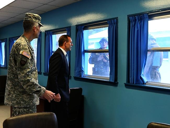 Face to face ... Colonel James Minnich with Prime Minister Tony Abbott in the T2 Building, with North Korean soldiers looking in.