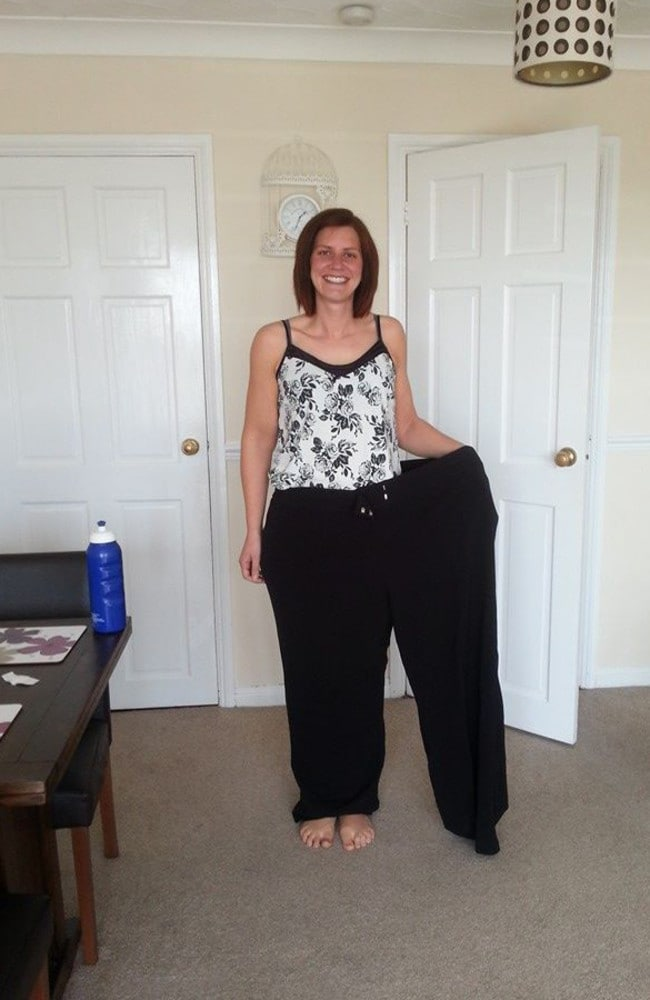 Donna showing off her transformation with a pair of her old trousers. Photo: Austral Scope