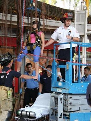 Back on terra firma ... The terrified woman, 23, is brought down in a harness after being stuck in branch 7.6 metres up. Picture: Miami Fire Rescue