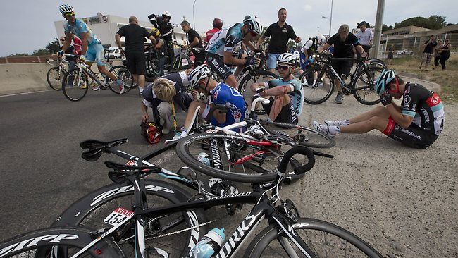 Murilo Antoniobil Fischer of Brazil, center left, Tony Martin of Germany, center right, and Tony Gallopin of France, right, wait for medical assistance after crashing in the last kilometers of the first stage of the Tour de France. (AP Photo/Joel Saget,)