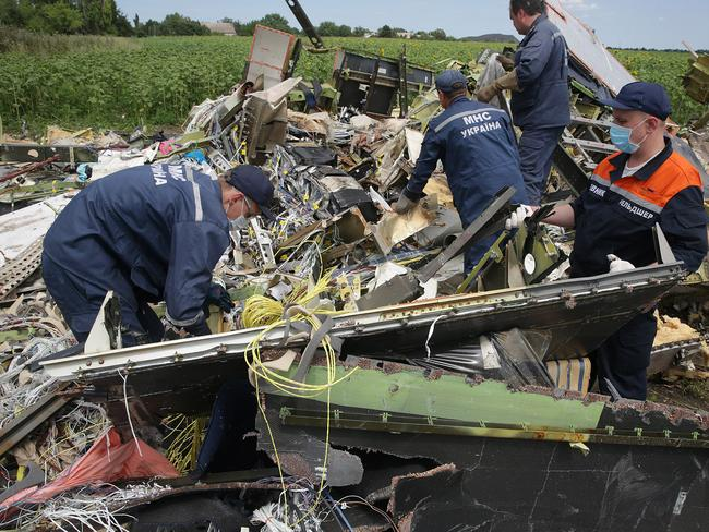 Destroying evidence3 ... local emergency workers angle grind into the remains of the cockpit of MH17 with suspicion of a body below in the village of Rassypnoye. Picture: Ella Pellegrini