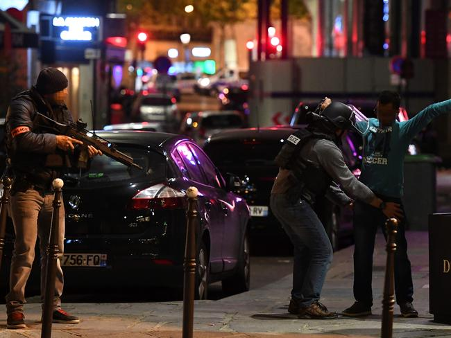 Police officers frisk a man on the Champs Elysees in Paris after the deadly shooting.