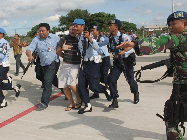 Escorted into questioning ... Matt Lockley is handcuffed and pushed by Indonesian Air Force soldiers into Ngurah Rai airport in Denpasar.