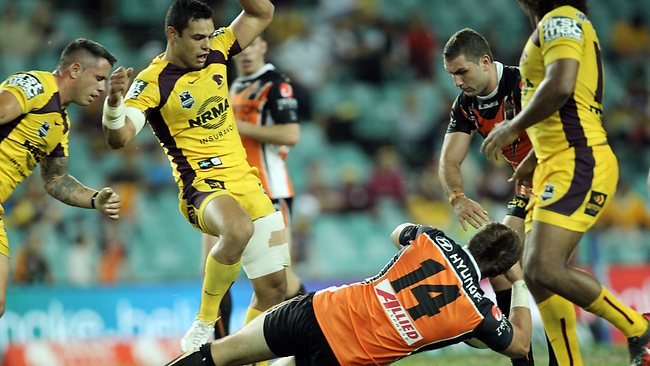 Tigers forward Matt Groat is left reeling by a hit from Bronco Ben Te'o. Picture: Mark Evans