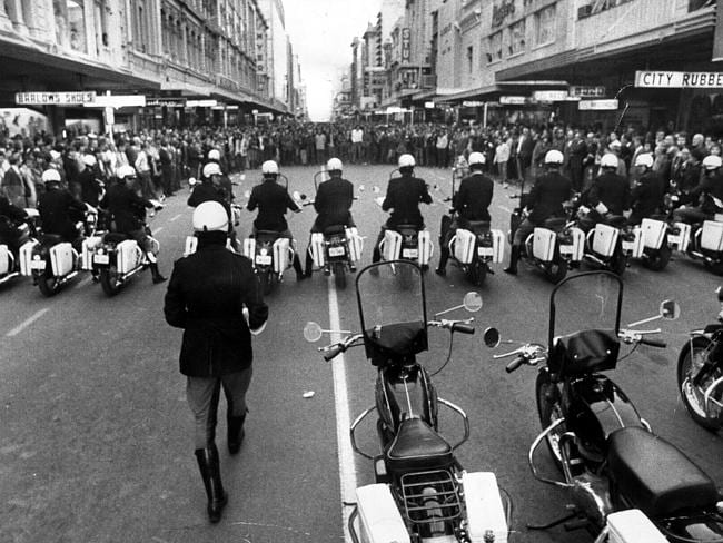Police motor cyclists form a barrier across Rundle St as hundreds of demonstrators march down the road during an anti-Vietnam War protest in 1971.