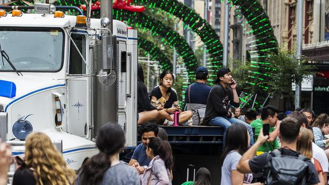 Shoppers sit on a parked truck in Sydney's CBD. Picture: Jenny Evans