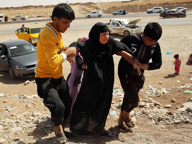 An elderly woman is helped into a temporary displacement camp for Iraqis caught-up in the fighting in and around the city of Mosul, Iraq. Picture: Spencer Platt/Getty Images