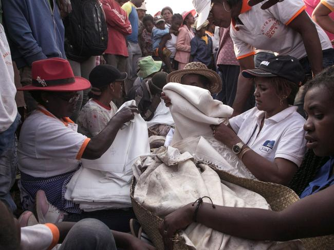 "During the Famadihana, which can be translated as ""turning of the bones"", several crypts are opened and people take the bodies of their ancestors from the family crypts and rewrap them in fresh cloth, then dance with the corpses in their arms at the pace of traditional Malagasy music. Picture: AFP/RIJASOLO"