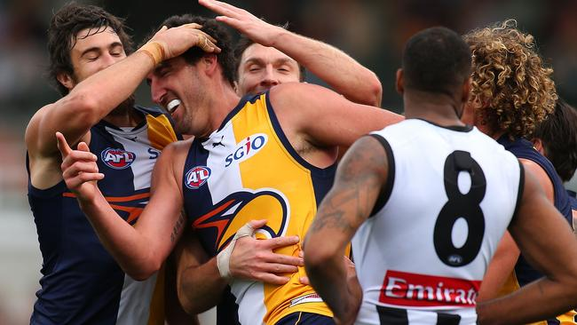 Dean Cox is mobbed by teammates after kicking a final quarter goal.