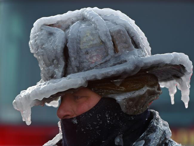 Firefighter Bobby Lehman, with his helmet and bunker gear caked in ice, tries to thaw out after battling a stubborn, wind-driven fire in Massachusetts on January 1, 2018. Picture:Christopher Evans/Boston Herald/Polaris/australscope