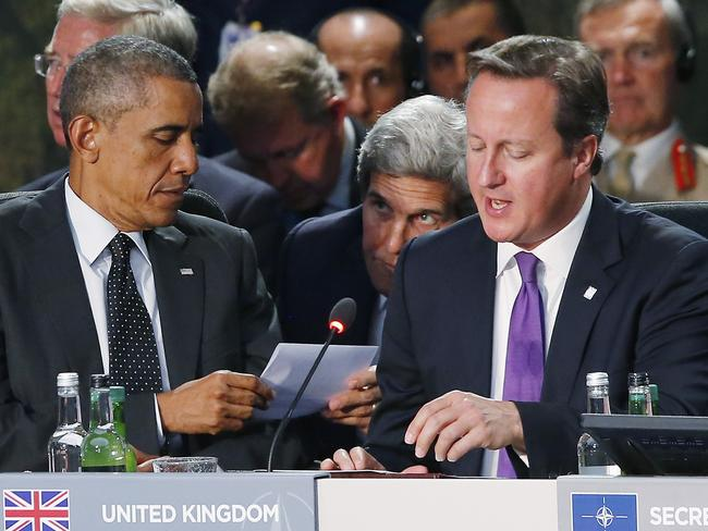 NATO meeting ... Secretary of State John Kerry (centre) passes a piece of paper to President Barack Obama as British Prime Minister David Cameron speaks during a meeting of NATO leaders in Wales. Picture: AP