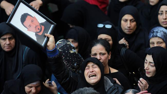 A relative of Samer Huhu, who was killed in a twin bombing attack that rocked a busy shopping street in Beirut, waves his portrait as she mourns during his funeral on November 13, 2015. Lebanon mourned 44 people killed in the bloodiest such attack in years. Picture: Joseph Eid / AFP
